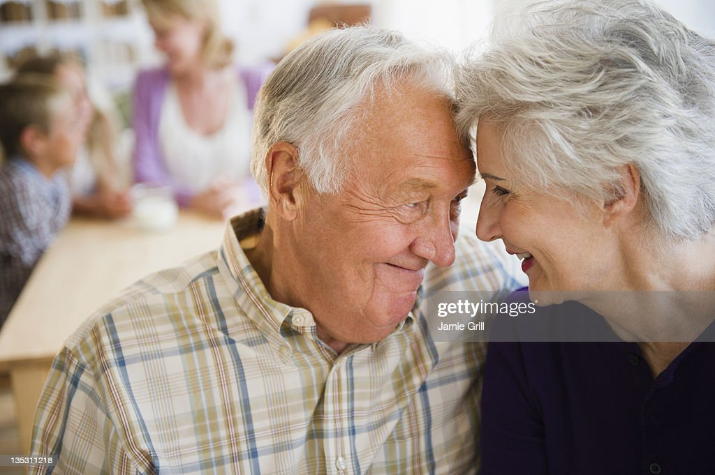 Senior couple embracing, family in background : Stock Photo