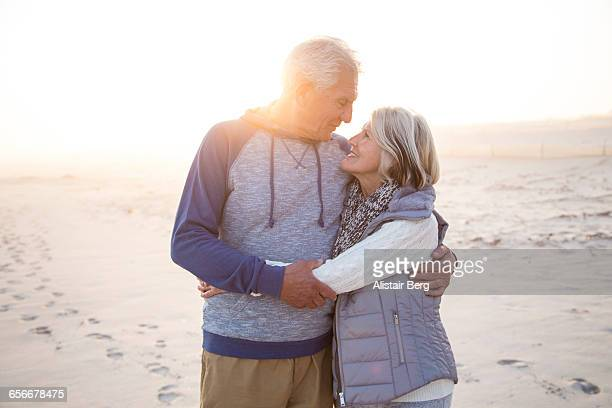 Senior couple embracing on a beach together