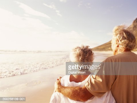 Senior couple embracing on beach, rear view : Stock Photo
