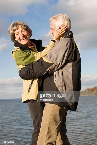 'Senior couple embracing, smiling'