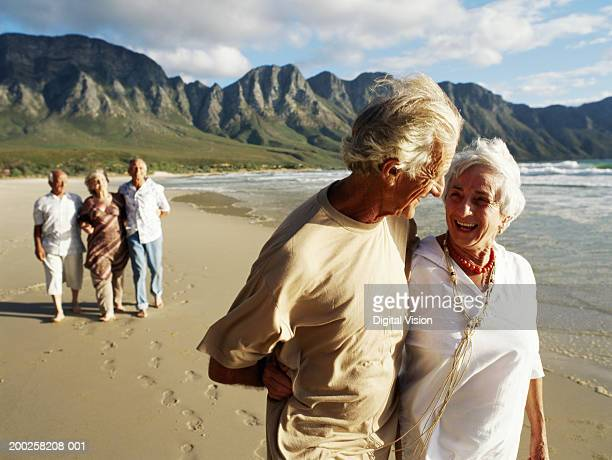 Senior couple embracing, walking on beach, friends in background