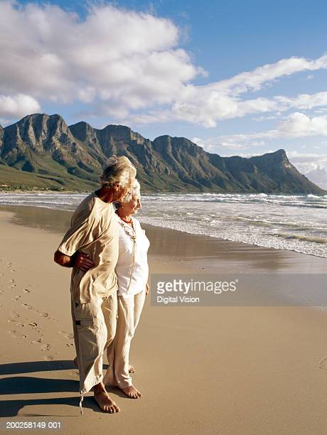 Senior couple embracing, walking on beach
