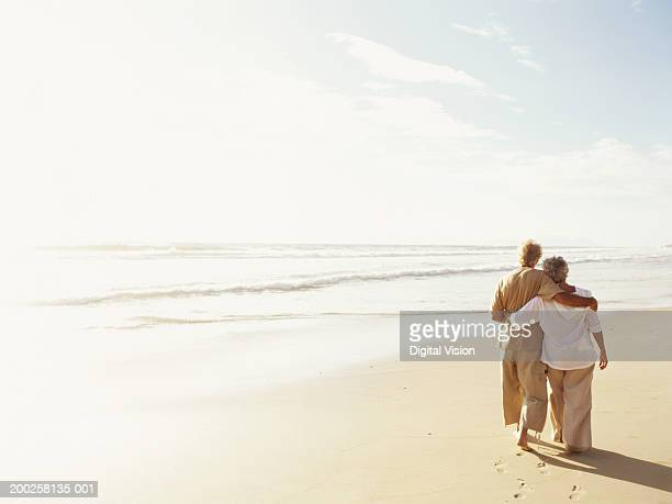 Senior couple embracing, walking on beach, rear view