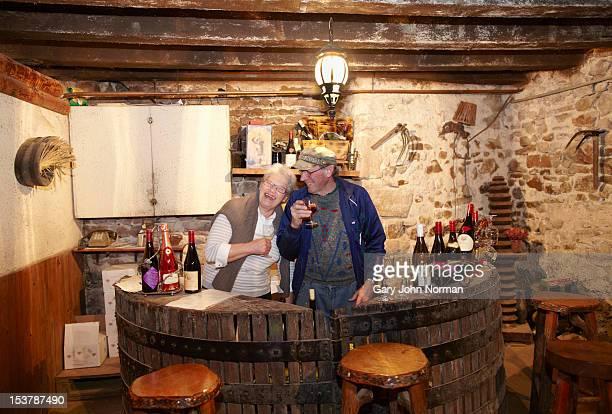 senior couple enjoy wine from their cellar
