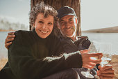 Portrait of loving mature couple sitting together with a glass of wine. Man and woman camping near a lake on a summer day.