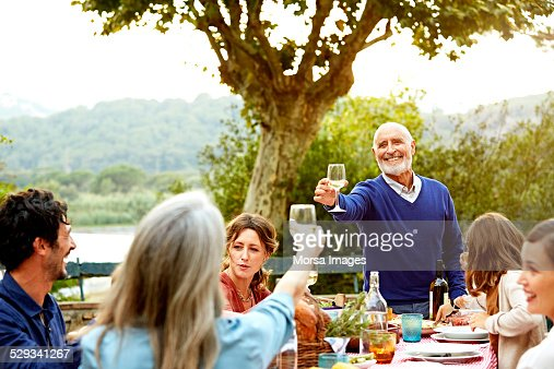 Senior couple enjoying meal with family in yard