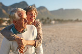 Portrait of happy mature man carrying his beautiful wife on his back at the beach. Senior couple enjoying their vacation at the sea shore.