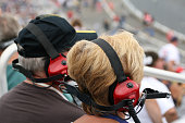 Senior Couple Fans Wearing Earmuffs at Racing Event