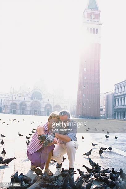 Senior couple feeding pigeons in St. Mark's Square, Venice, Veneto, Italy