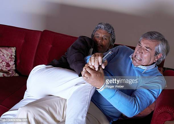 Senior couple fighting for remote control on sofa