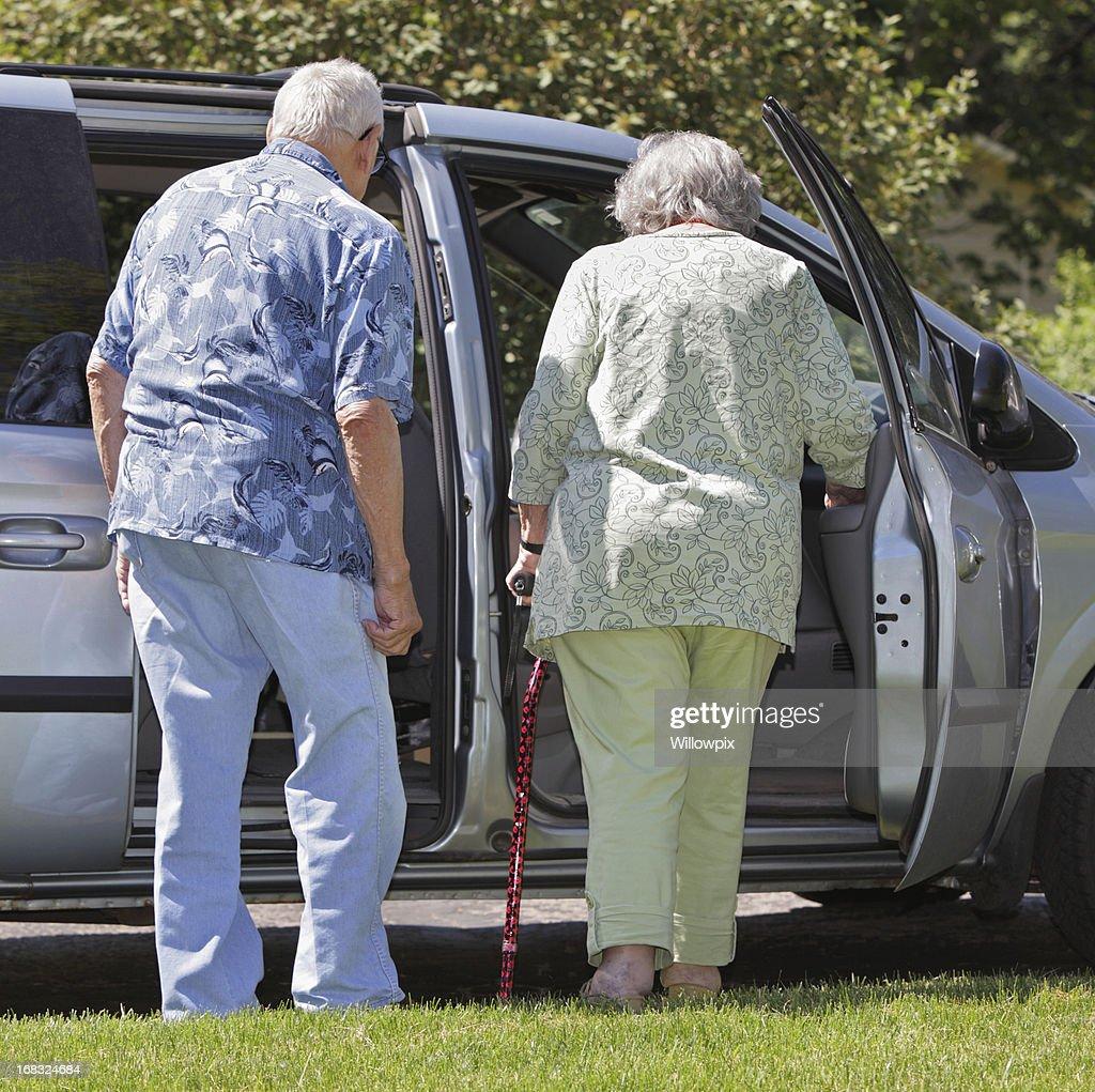 Senior Couple Getting Into Minivan Car