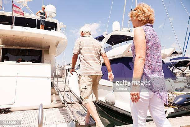 senior couple getting on their yacht