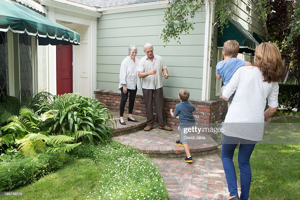 Senior couple greeting family at home