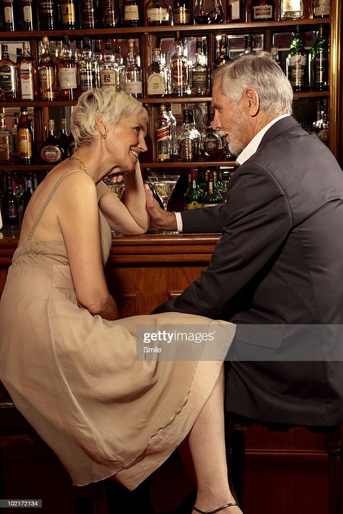Senior couple having conversation in bar : Stock Photo
