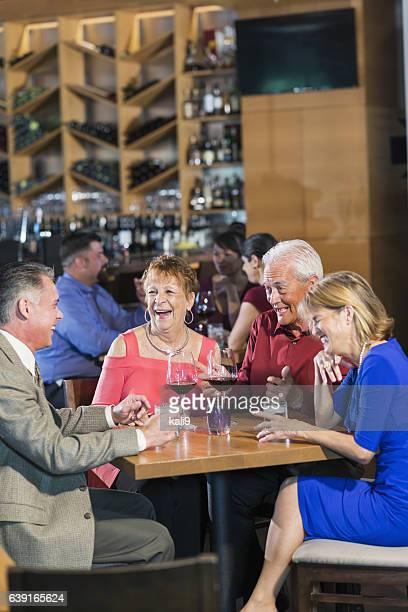 Senior couple having drinks in restaurant with friends