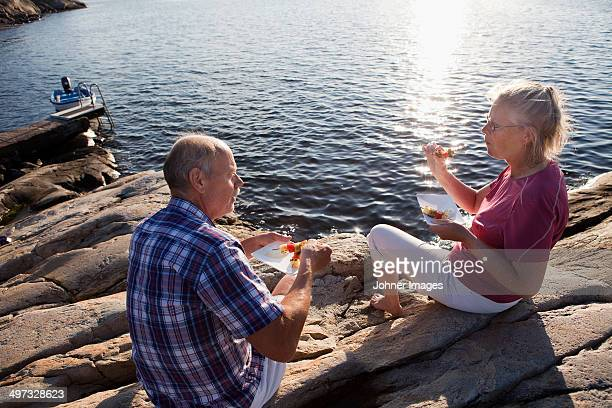 Senior couple having food on cliff, Bohuslan, Sweden