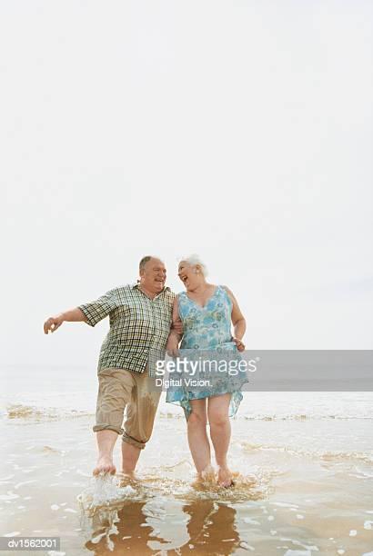 Senior Couple Having Fun at Water's Edge