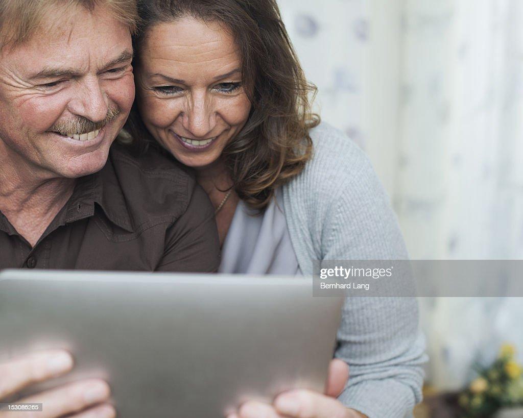Senior couple having fun using tablet : Stock Photo