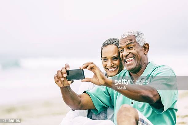 Senior couple having fun with smart phone on beach