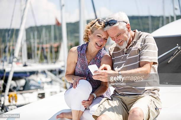 年配のカップルが楽しく、スマートフォンのヨット