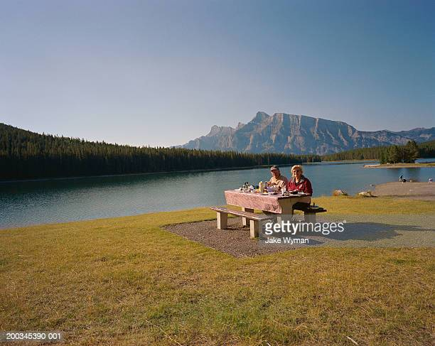 Senior couple having picnic near lake, portrait