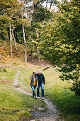 Senior couple are hiking through woodlands in the Lake District.