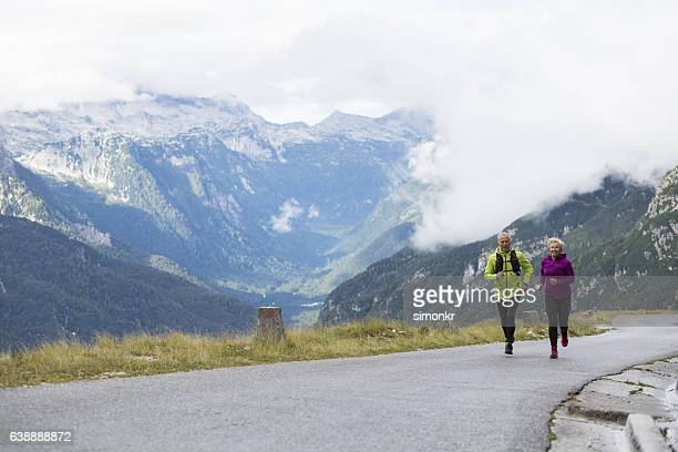 Senior couple hiking on road