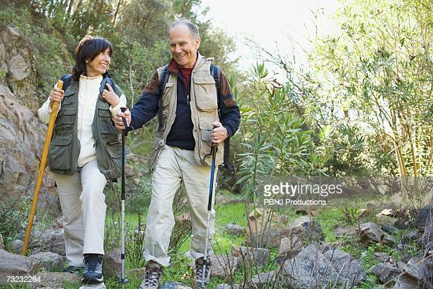 Senior couple hiking with poles