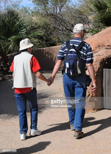 A senior couple hold hands as they visit the ArizonaSonora Desert Museum in Saguaro National Park near Tucson Arizona