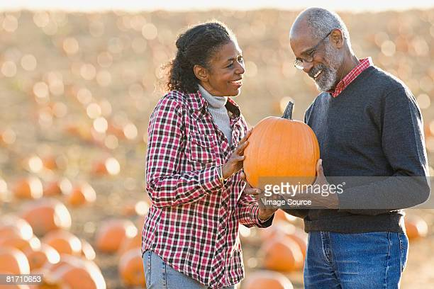 A senior couple holding a pumpkin