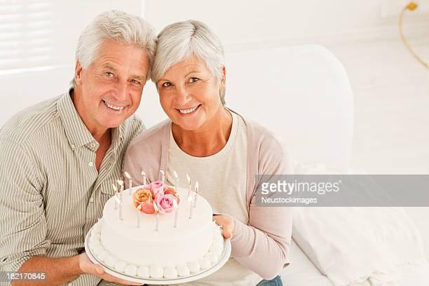 senior couple holding anniversary cake