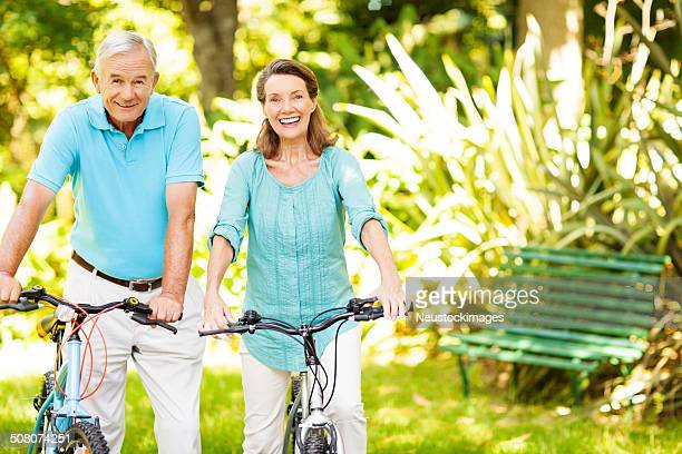 Senior Couple Holding Bicycles In Park