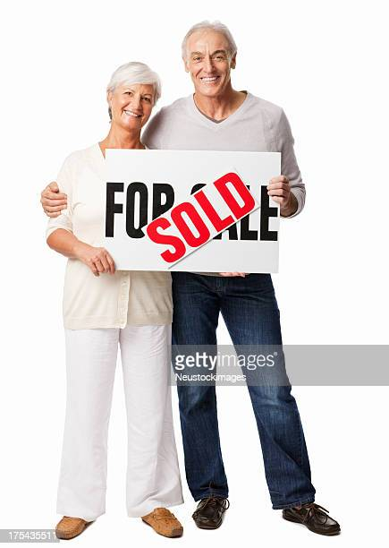 Senior Couple Holding 'For Sale' and 'Sale' Sign Board-Isolated