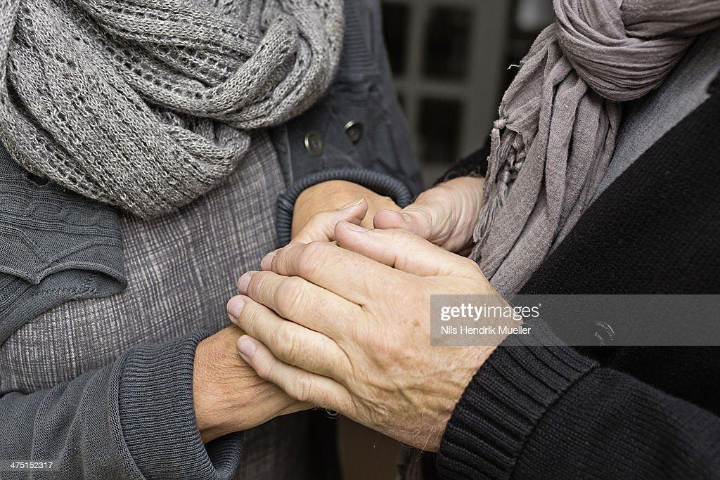 Senior couple holding hands, close up