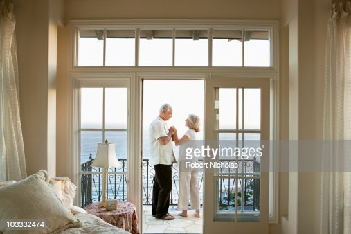 Senior couple holding hands face to face on balcony for Balcony overlooking ocean