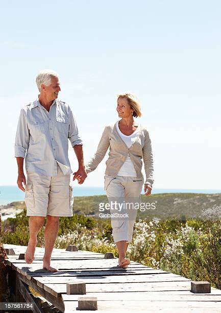 Senior couple holding hands on a boardwalk by the beach