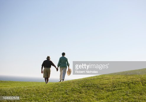Senior couple holding hands on grassy hill : Stock Photo