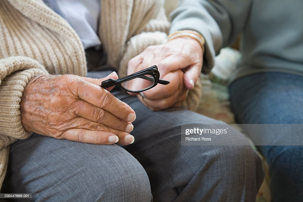 Senior couple holding hands (mid section) : Stock Photo