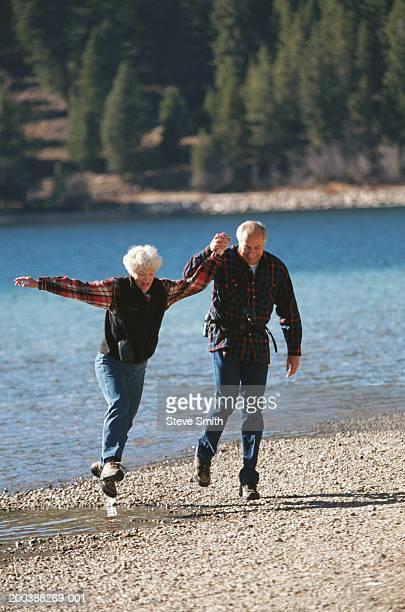 Senior couple holding hands, running on beach
