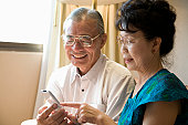 Senior couple holding mobile phone, smiling