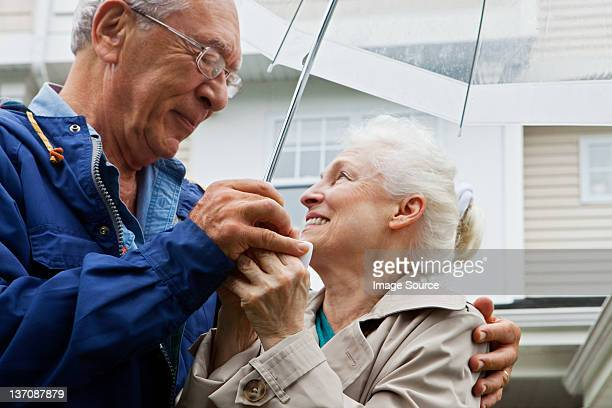 Senior couple holding umbrella outside