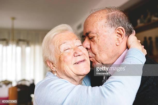 Senior couple hugging and kissing at home