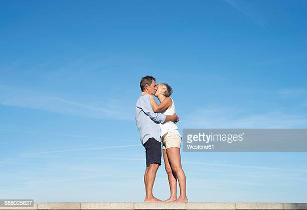 Senior couple hugging and kissing on a wall in front of sky