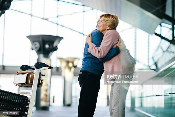 Senior Couple Hugging At The Airport