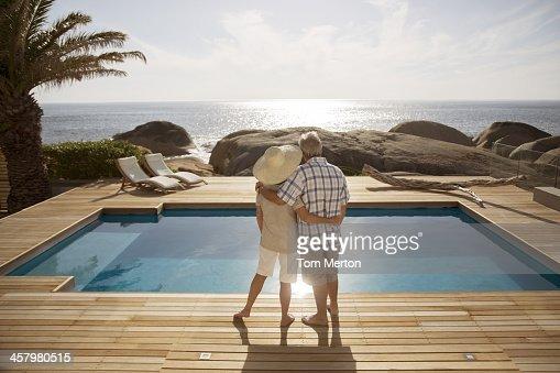 Senior couple hugging by modern pool overlooking ocean