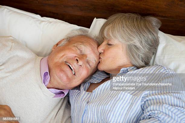 Senior couple hugging in bed