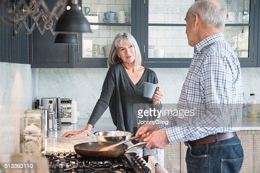 Senior couple in a kitchen making dinner and talking