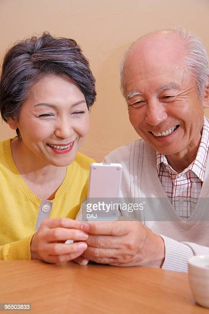 Senior couple in a kotatsu looking at cell phone