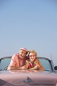 Senior couple in a pink convertible
