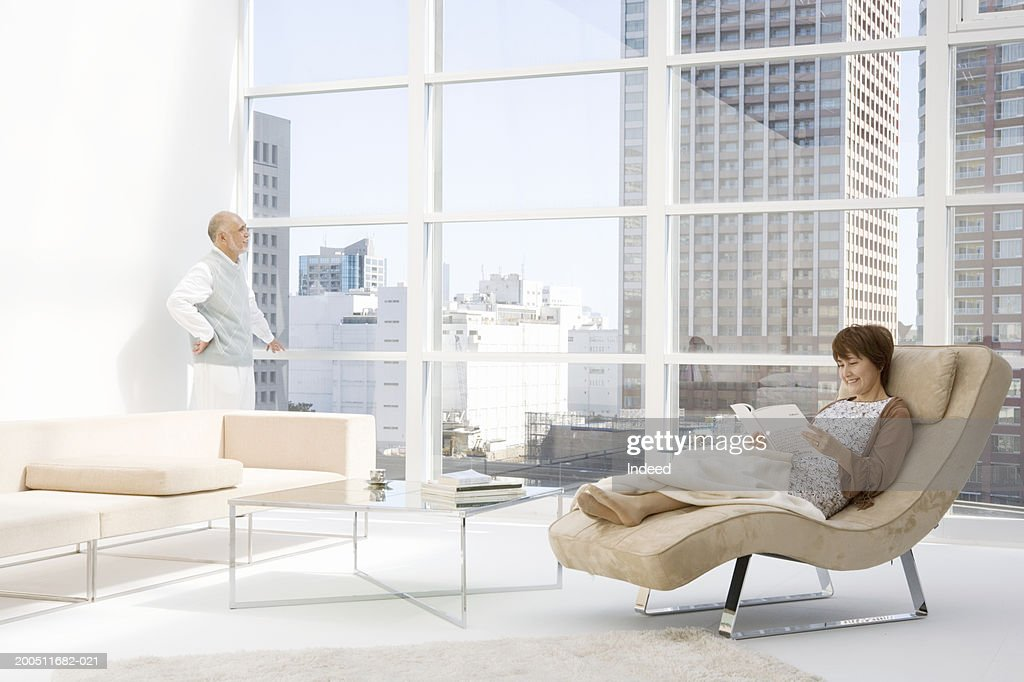 Senior couple in apartment, woman on chaise longue, man by window
